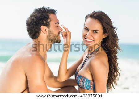 Happy girlfriend putting sunscreen on boyfriends nose on a sunny day - stock photo