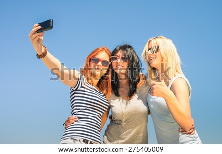Happy girlfriends taking selfie against blue sky - Friendship summer concept with new trends and technology - Best friends enjoying moments with modern smartphone - Warm sunny afternoon color tones - stock photo