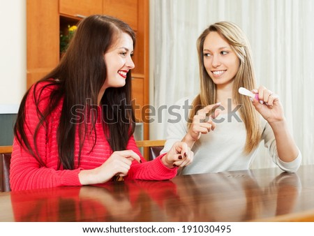 Happy girlfriends with pregnancy test at home interior