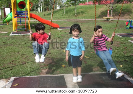 Happy girls and boy swinging in the park - stock photo