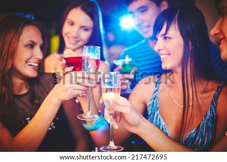 Happy girls and guys toasting at party - stock photo