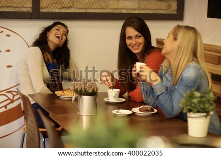 Happy girls chatting in cafeteria, having coffee and biscuit.