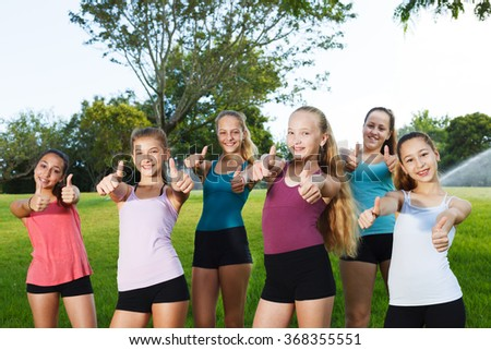 Happy girls holding thumbs up at summer camp - stock photo
