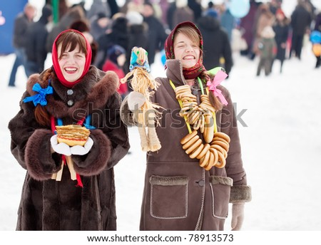 Happy girls in russian traditional clothes with pancake and round cracknel during  Shrovetide - stock photo