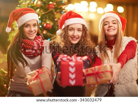 Happy girls in Santa caps looking at camera with presents in hands - stock photo