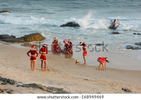 happy girls in Santa Clause suit having fun on the beach - stock photo