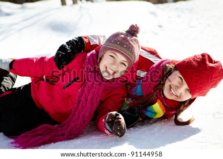 Happy girls in winterwear looking at camera while playing outside - stock photo