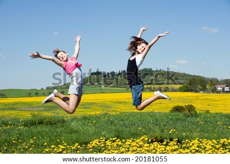 happy girls jump in field under blue sky and clouds - stock photo