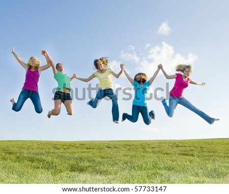 Happy girls jumping for joy with blue sky in the background - stock photo