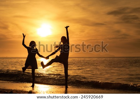Happy girls jumping on the beach at the sunset time.