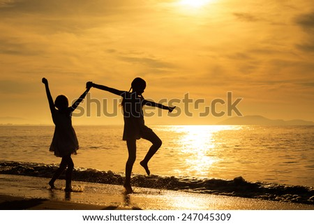 Happy girls jumping on the beach at the sunset time. - stock photo