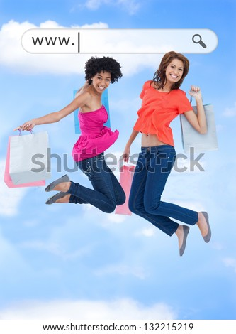 Happy girls jumping with their shopping bags under address bar on blue sky background