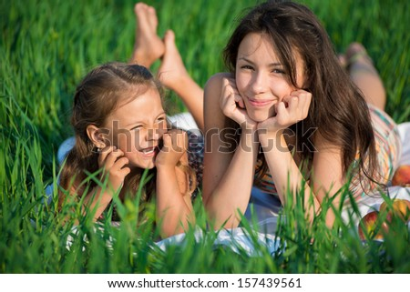 Happy girls on green grass at spring or summer park picnic - stock photo