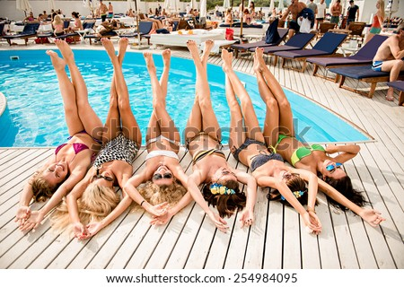 happy girls on the beach. beautiful girlfriends lie on white wooden floor near the pool. girls lying on their backs - stock photo