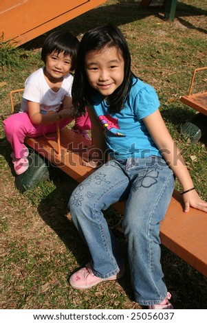 Happy girls playing seesaw at the playground in the park on sunny day - stock photo