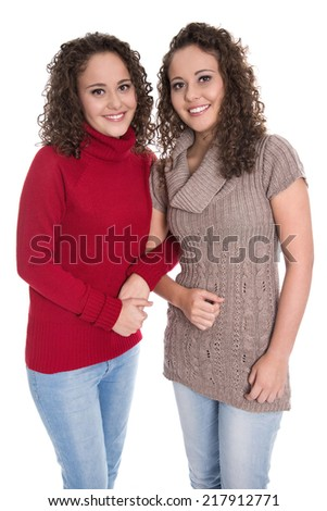 Happy girls: Portrait of real female twins wearing winter pullover.