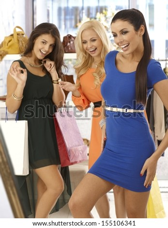 Happy girls shopping together, one trying on blue mini dress, friends looking at her with joy. - stock photo