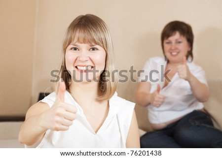 Happy girls showing thumb up sign in home
