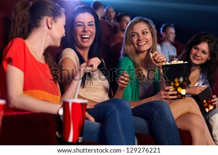 Happy girls sitting in multiplex movie theater, talking, laughing. - stock photo