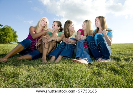 Happy girls sitting together in the grass and laughing