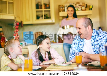 Happy girls talking to their father in the kitchen with mother on background - stock photo