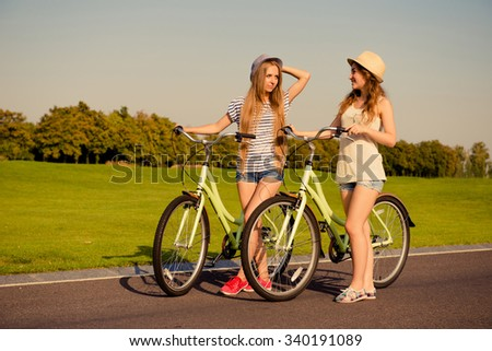 happy girls together to ride a bicycle - stock photo