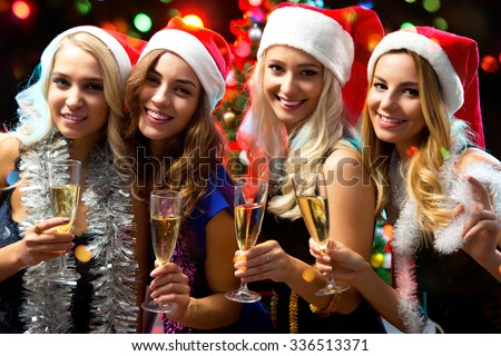 Happy girls touching the glasses with each other - stock photo