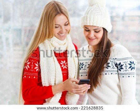 Happy girls using app on a mobile phone sending Christmas messsage - stock photo