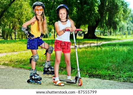 Happy girls with roller and scooter in a summer park. - stock photo