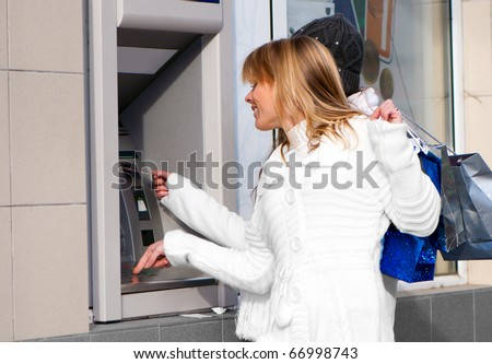 Happy girls withdrawing money from credit card at ATM - stock photo