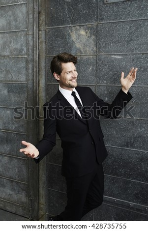 Happy go lucky businessman in black, smiling - stock photo