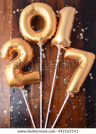 Happy 2017 gold New Year Balloons with glitter stars on dark wood table background.