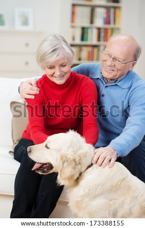 Happy golden retriever with its elderly owners panting happily as it is being stroked by a senior couple sitting in their living room - stock photo