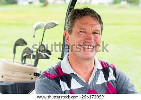 Happy golfer driving his golf buggy smiling at camera on a sunny day at the golf course - stock photo