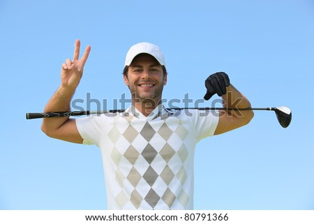Happy golfer giving peace sign - stock photo