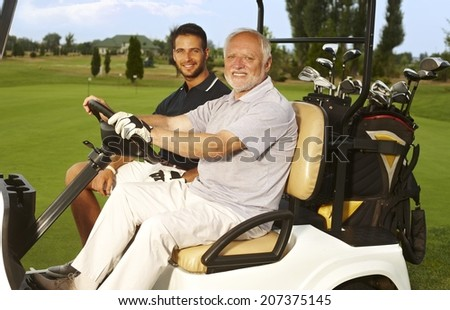 Happy golfers sitting in golf cart, smiling, looking at camera. - stock photo