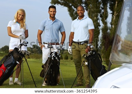 Happy golfers standing on golf fields with golfing kit, looking at camera, smiling. - stock photo