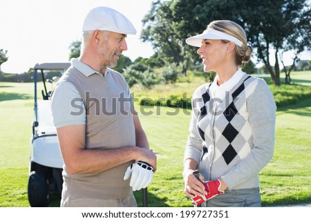 Happy golfing couple chatting with golf buggy behind on a sunny day at the golf course - stock photo