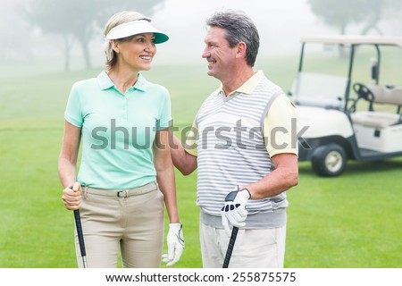 Happy golfing couple facing each other with golf buggy behind on a foggy day at the golf course - stock photo