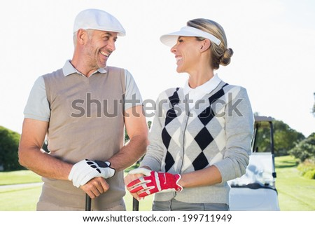 Happy golfing couple facing each other with golf buggy behind on a sunny day at the golf course - stock photo