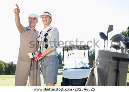 Happy golfing couple pointing with golf buggy behind on a sunny day at the golf course - stock photo