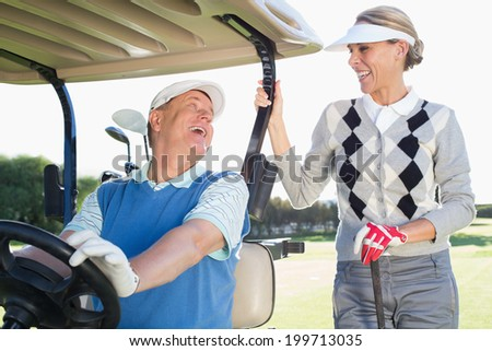 Happy golfing couple setting out for the day on buggy on a sunny day at the golf course - stock photo