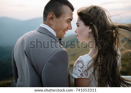 Happy gorgeous bride and groom walking in sun light holding hands, boho wedding couple, luxury ceremony at mountains with amazing view, space for text