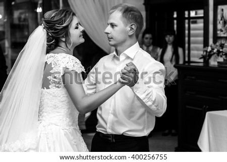 happy gorgeous bride and stylish groom dancing in rich restaurant with tender feelings, romantic moment