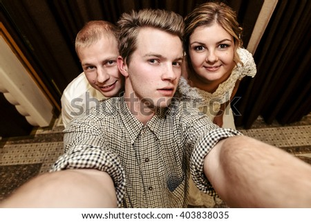 happy gorgeous bride and stylish groom taking photo selfie with photographer, funny moment at wedding reception - stock photo