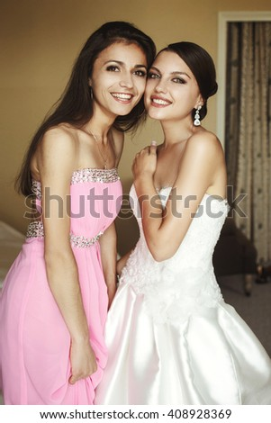 Happy gorgeous brunette bride in white dress having fun with beautiful bridesmaids - stock photo