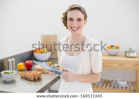 Happy gorgeous woman holding her tablet standing in her kitchen smiling at camera