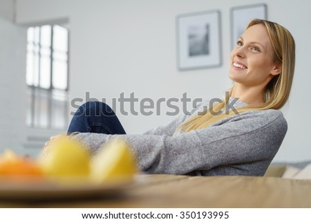 Happy gorgeous young woman sitting daydreaming at home looking up into the air with a faraway expression and smile of pleasure, low angle view over the dining table and fresh fruit - stock photo