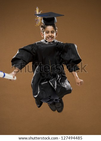 Happy graduate boy with mortarboard and diploma jumping - stock photo