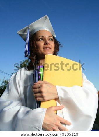 Happy graduate female student holding a big pile of textbooks and folders - stock photo